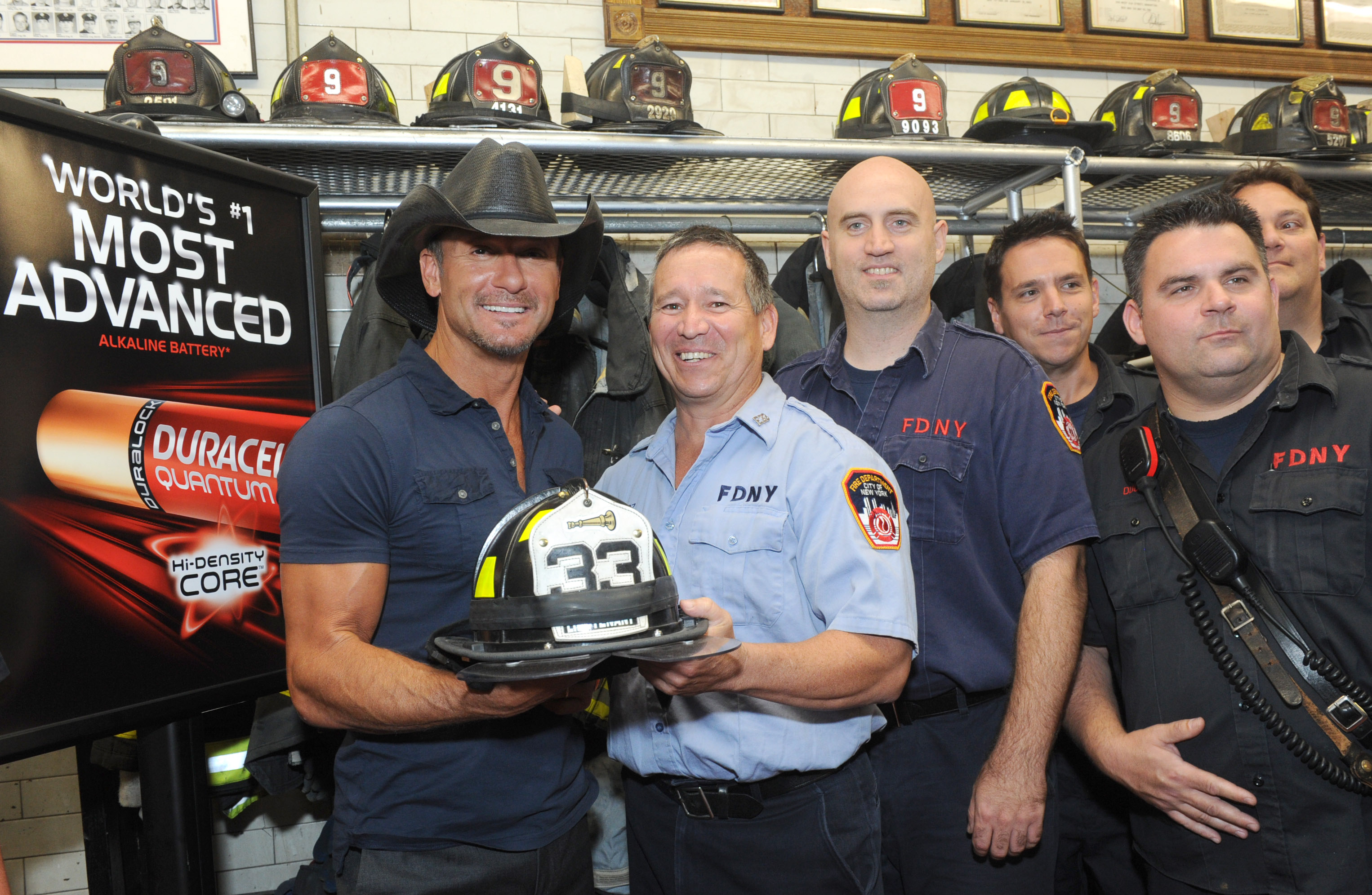 Country music star Tim McGraw with members of the FDNY at the launch event of Duracell's new Quantum battery and announces the donation of one million of these most powerful batteries to first responders, Thursday, Aug. 15, 2013, at an FDNY firehouse in New York. (Diane Bondareff/Invision for Duracell)
